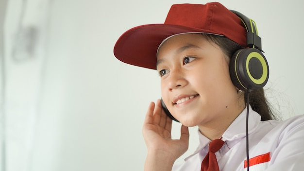 Azjatycka uczennica szkoły podstawowej ucząca się online w domu, słuchająca za pomocą słuchawek