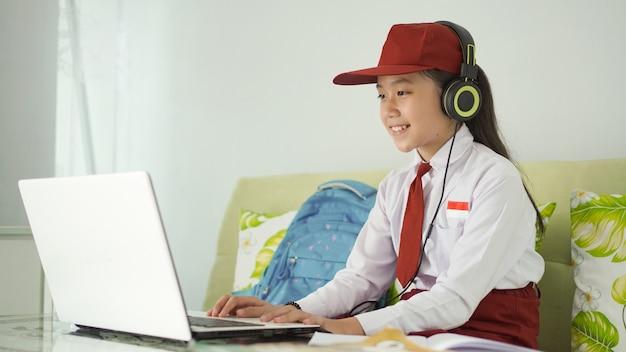 Azjatycka uczennica szkoły podstawowej uczy się online za pomocą laptopa w domu
