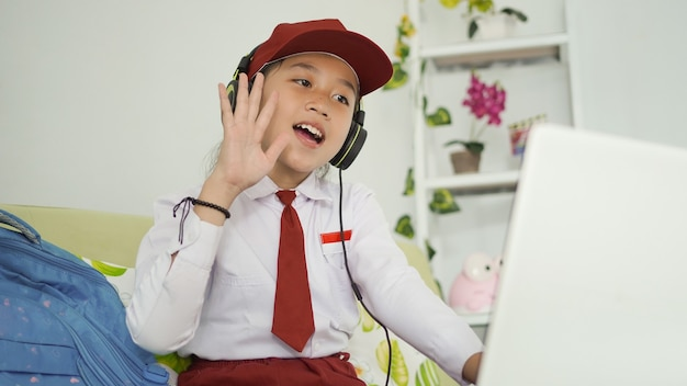 Azjatycka uczennica szkoły podstawowej uczy się powitania online na ekranie laptopa w domu
