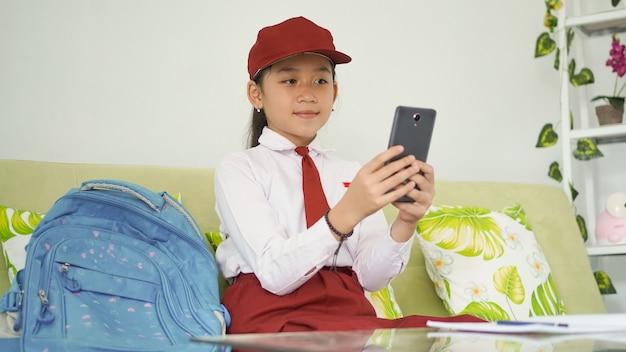 Azjatycka uczennica szkoły podstawowej uczy się w domu swoim smartfonem