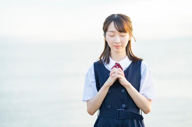 Azjatycka uczennica szkoły średniej w modlitwie stanowią na zewnątrz