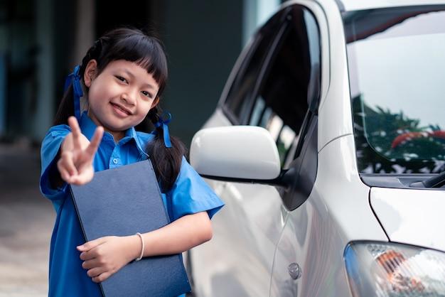 Azjatycka uczennica trzyma książkę ze stojącą stroną samochodu. powrót do koncepcji szkoły