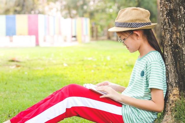Azjatycka uczennica w kapeluszu siedziała czytając książkę pod wielkim drzewem.