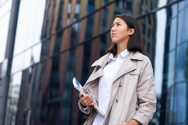 Azjatycka ufna młoda bizneswoman pozycja na zewnątrz budynku biurowego z książkami, podręcznikami lub dokumentami.