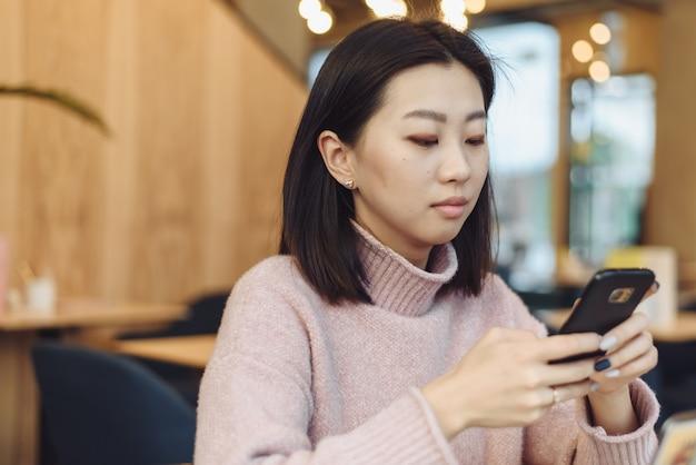 Azjatycka urocza dziewczyna wspina się na telefonie w sklep z kawą. dość piękna kobieta szuka informacji w internecie lub pracuje
