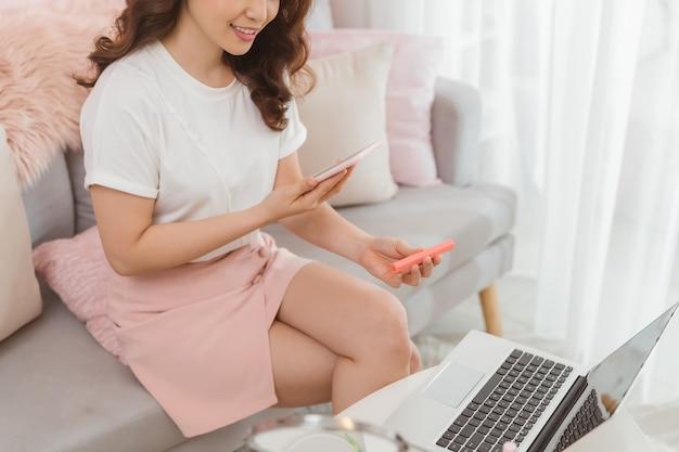 Azjatycka uśmiechnięta dziewczyna używa smartfona do robienia szminki wystawionej na sprzedaż w internecie. właściciel małej firmy rozpoczynającej pracę z tabletem w miejscu pracy