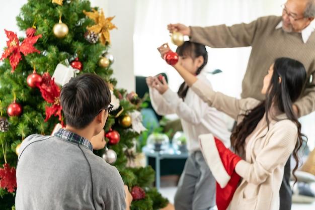 Azjatycka wielopokoleniowa rodzina dekorująca choinkę.