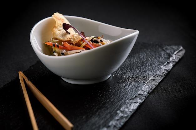 Azjatycka z makaronem miso, sosem sojowym, ziołami. na czarnym kamiennym stole z pałeczkami. skopiuj widok z góry