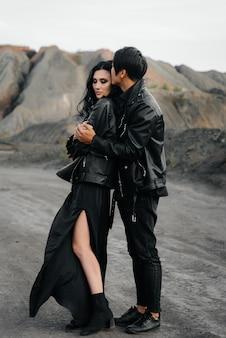 Azjatycka zakochana para w czarnych skórzanych ubraniach spaceruje wśród drzew. styl, moda, miłość