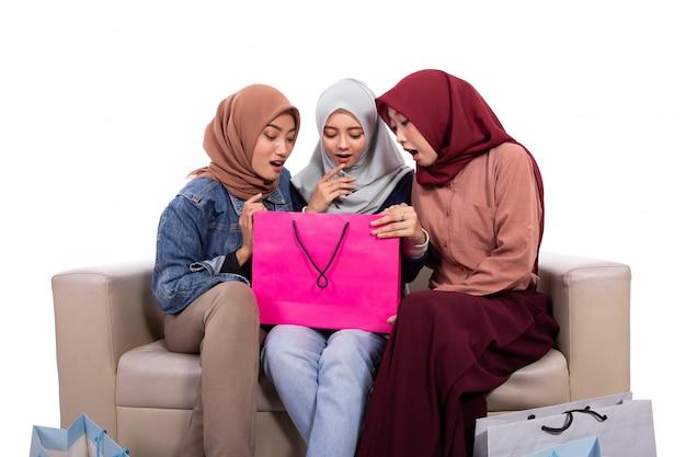 Azjatycka zawoalowana kobieta podekscytowana po otwarciu torby na zakupy