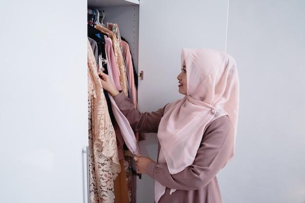 Azjatycka zawoalowana kobieta wyjmuje ubrania z szafy