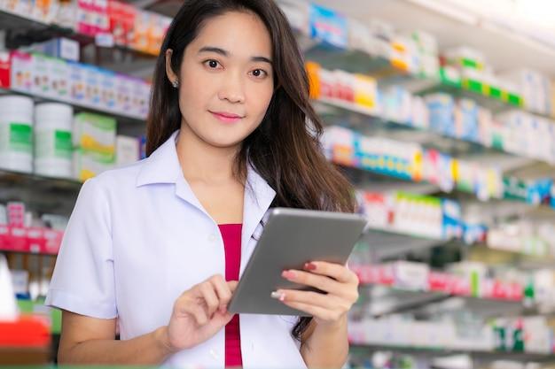 Azjatycka żeńska farmaceuta używa cyfrową pastylkę w aptece