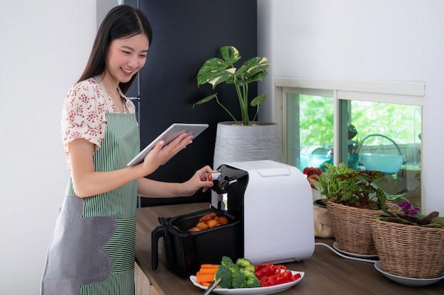 Azjatycka żona zrobiła bezolejową frytkownicę powietrzną do gotowania smażonego kurczaka na dzisiejszy obiad, ten obraz może być użyty do koncepcji żywności, kuchni i technologii.