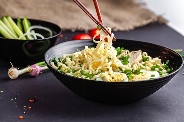 Azjatycka zupa ramen z kurczakiem, jajkiem, szczypiorkiem w czarnej misce na stole. miska z makaronem ramen