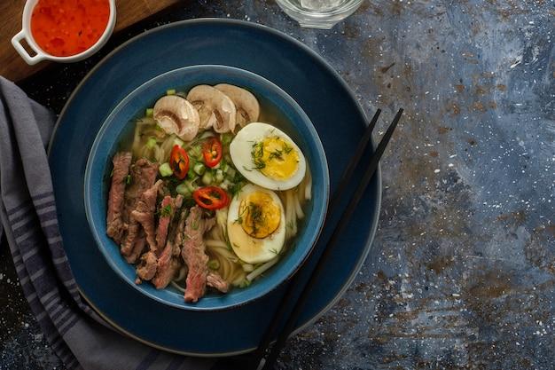 Azjatycka zupa ramen z wołowiną, jajkiem, szczypiorkiem, grzybami w misce na ciemno. copyspace. widok z góry