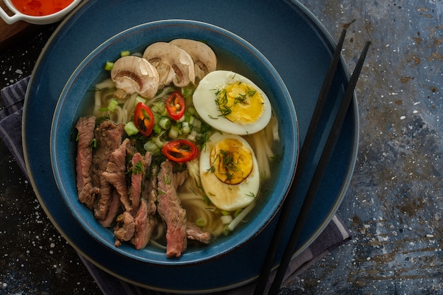 Azjatycka zupa ramen z wołowiną, jajkiem, szczypiorkiem, grzybami w misce na ciemno.