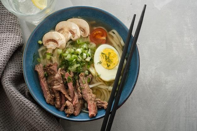 Azjatycka zupa ramen z wołowiną, jajkiem, szczypiorkiem i grzybami w misce. copyspace