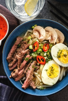 Azjatycka zupa ramen z wołowiną, jajkiem, szczypiorkiem i grzybami w misce. widok z góry