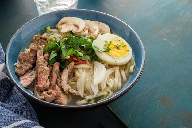 Azjatycka zupa ramen z wołowiną, jajkiem, szczypiorkiem i grzybami w misce.