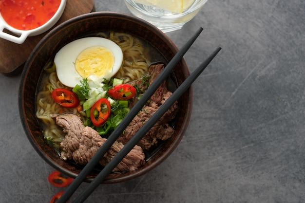 Azjatycka zupa ramen z wołowiną, jajkiem, szczypiorkiem w misce na szaro. copyspace. widok z góry