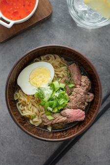 Azjatycka zupa ramen z wołowiną, jajkiem, szczypiorkiem w misce na szaro.