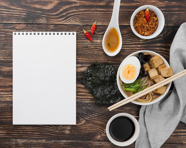 Azjatycka zupa z makaronem ramen i notatnik