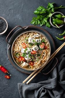 Azjatycka zupa z makaronem, ramen z tofu i warzywami na ciemnej powierzchni, widok z góry