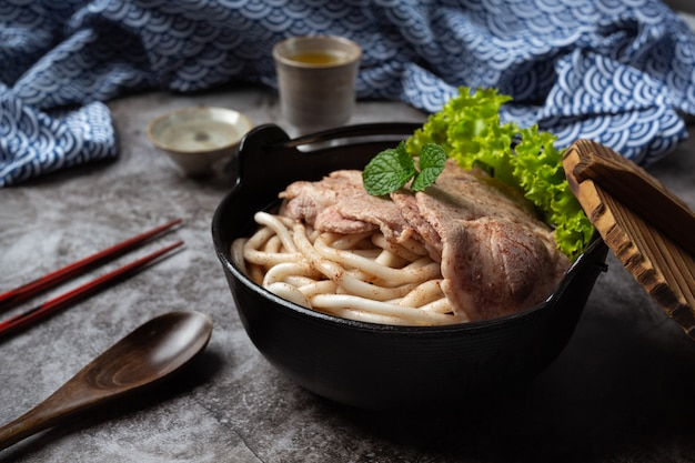 Azjatycka zupa z makaronem, wieprzowiną i zieloną cebulą w misce na stole.