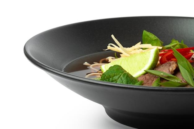 Azjatycka zupa z wołowiną i makaronem udon na białym tle