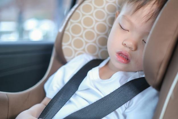Azjatycki 2-3-letni maluch chłopiec dziecko śpi w nowoczesnym foteliku samochodowym. bezpieczeństwo podróży dzieci na drodze