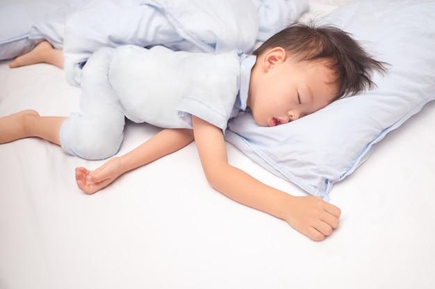 Azjatycki 3-4-letni chłopiec w piżamie śpi / drzemie na niebieskiej poduszce w łóżku