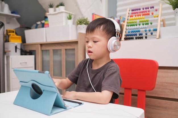 Azjatycki 4-letni berbeć chłopiec dziecko używa pastylka komputer osobistego komputer, kształcenie na odległość, aktywność dla przedszkola pojęcia