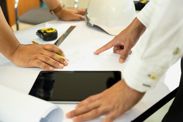 Azjatycki architectuer pracuje na plan rękach wskazuje przy bluepring nakreśleniem.
