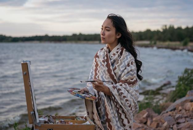 Azjatycki artysta malujący obraz na płótnie, szukający inspiracji, podziwia piękne krajobrazy