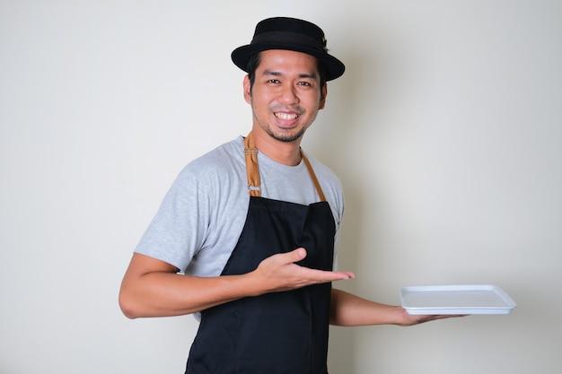 Azjatycki barista mężczyzna trzymający pustą tacę z uśmiechniętym, szczęśliwym wyrazem twarzy