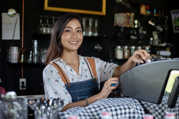 Azjatycki barista uśmiecha się i używa ekspresu do kawy w ladzie kawiarni