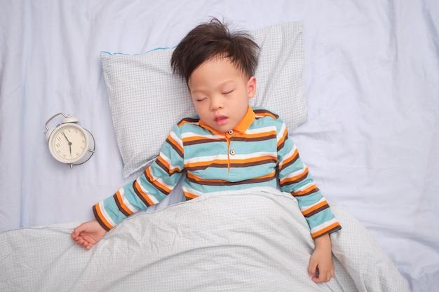 Azjatycki berbeć chłopiec dzieciak bierze drzemkę, śpi na jego plecy z budzikiem