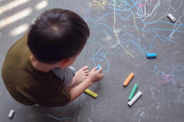 Azjatycki berbeć chłopiec dziecka rysunek z barwioną kredą na asfaltowym chodniczku outdoors, mały młody dzieciak bawić się samotnie