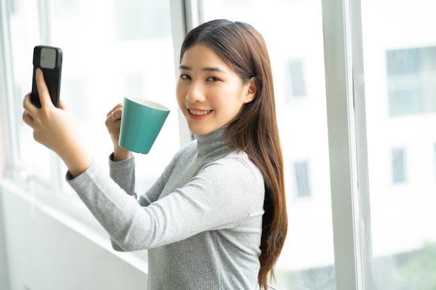 Azjatycki biznes kobieta stojąc przy selfie zdjęcie przez okno.
