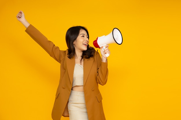 Azjatycki biznes kobieta trzyma megafon na białym tle na żółtej ścianie.