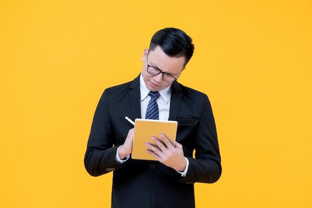 Azjatycki biznesmen bierze notatkę na cyfrowym pastylka komputerze