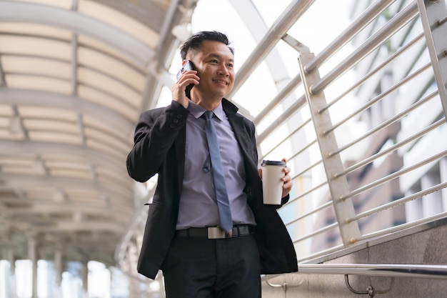 Azjatycki biznesmen chodzi i opowiada na telefonie komórkowym z biznesowymi budynkami biurowymi w miasta tle