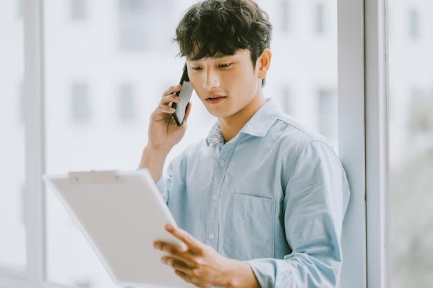 Azjatycki biznesmen dzwoni, aby porozmawiać o pracy przy oknie