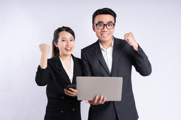 Azjatycki biznesmen i bizneswoman używający laptopa na białym tle