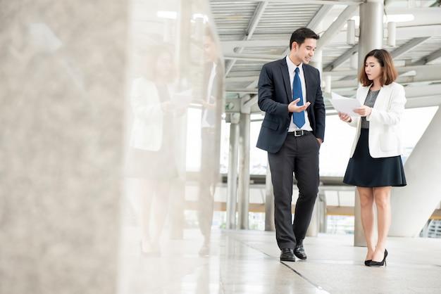 Azjatycki biznesmen i sekretarka chodzi pracę i dyskutuje