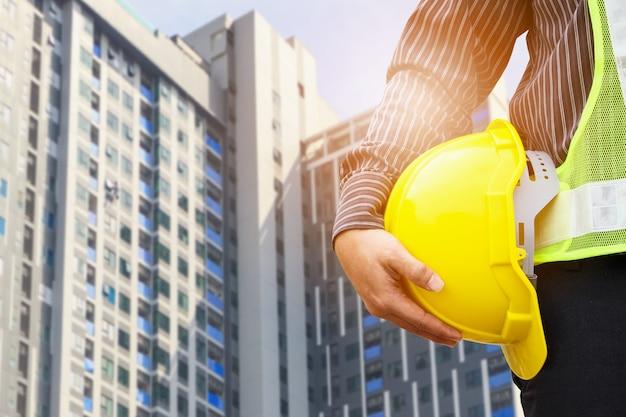 Azjatycki biznesmen inżynier budowlany lub pracownik architekta z żółtym kaskiem ochronnym na dużym placu budowy kondominium