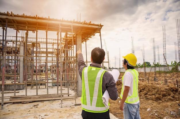 Azjatycki biznesmen kierownik budowy i pracownik inżyniera w kasku ochronnym trzymają papier pod ręką na placu budowy domu