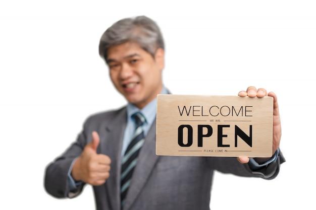 Azjatycki biznesmen nie nosi medycznych masek na odosobnionym tle i trzyma powitanie jesteśmy otwartym znakiem.