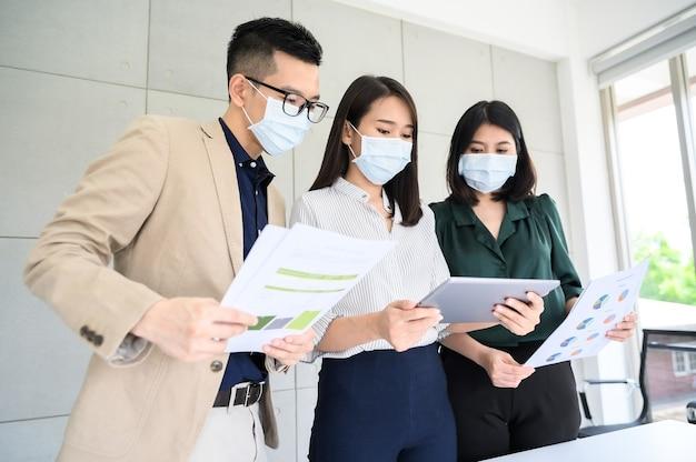 Azjatycki biznesmen nosi maskę na twarz omawia projekt w tablecie i papierze w sali konferencyjnej w nowoczesnym biurze