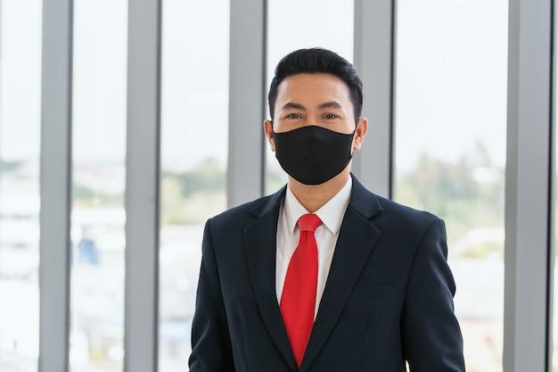 Azjatycki biznesmen noszący maskę w zapobieganiu koronawirusowi w biurze. koncepcja opieki zdrowotnej